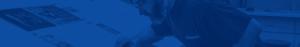 blue hued banner image of man at desk
